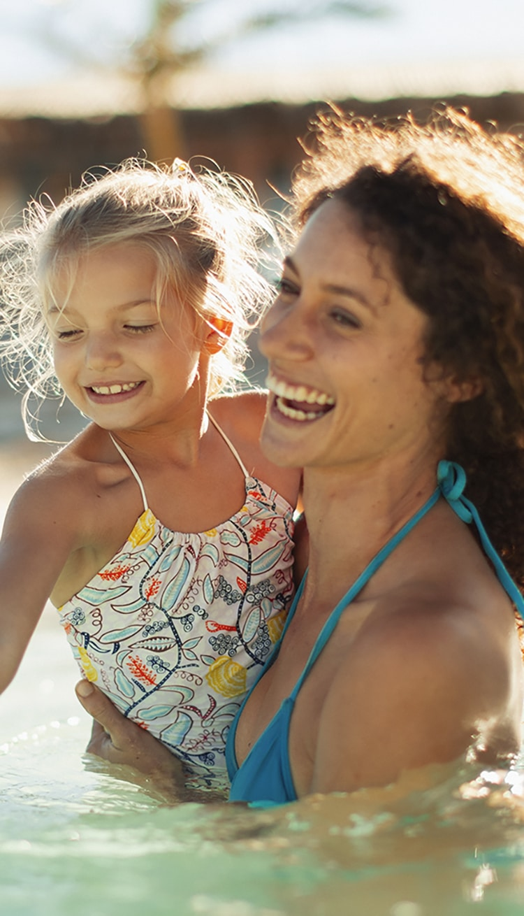 Happy mother and daughter swimming in sunny ocean
