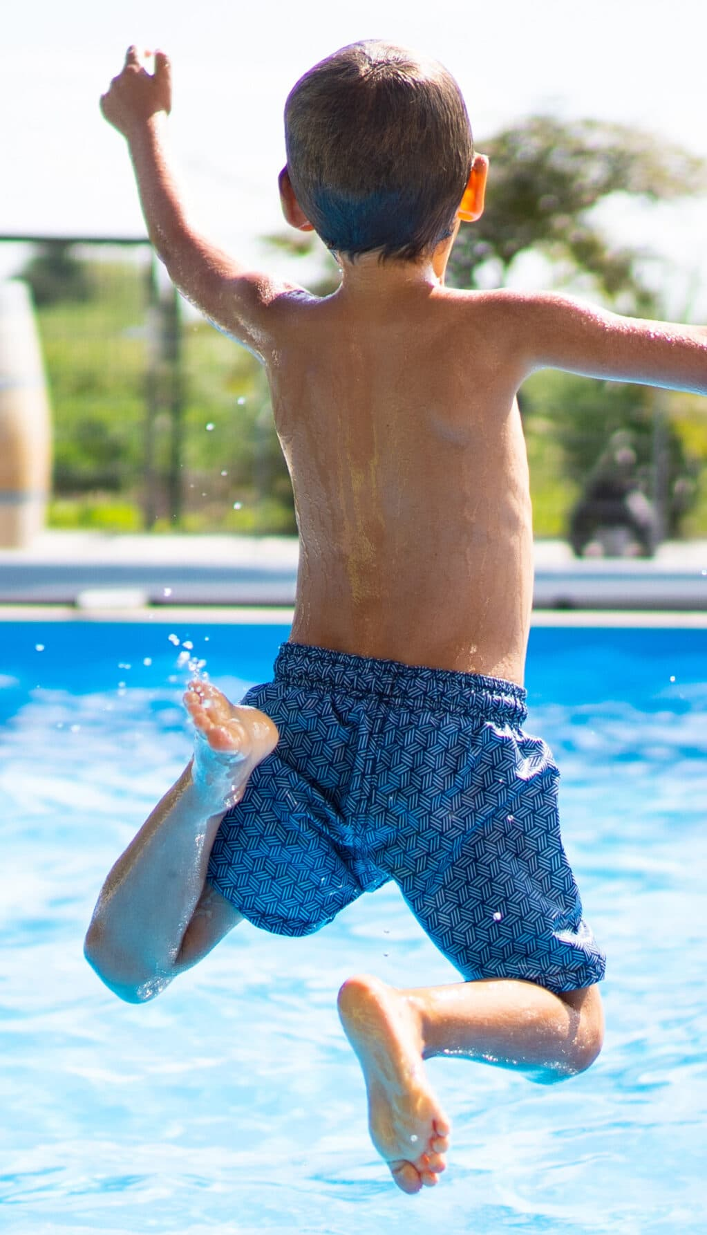 hello summer holidays – boy jumping in swimming pool