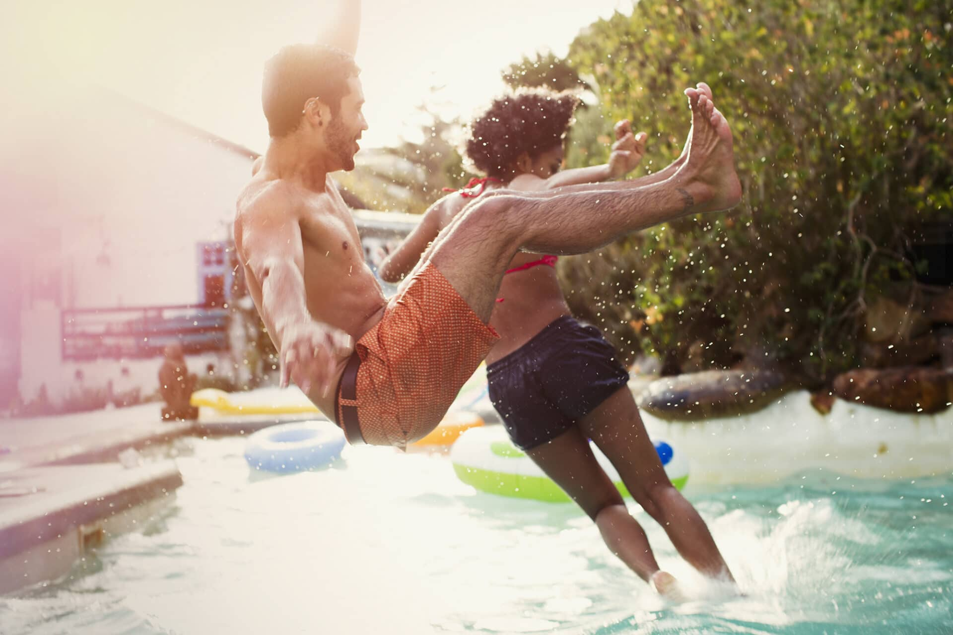 Friends jumping into swimming pool at pool party